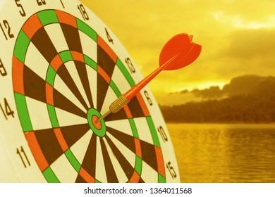 Dart arrow hitting in bullseye on dartboard with nature background.