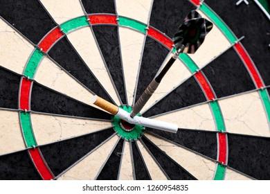Dart arrow hitting on cigarette with dartboard background, no smoking. Stop smoking concept.