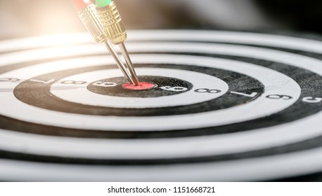 Dart arrow hitting in the target center of dartboard,business target