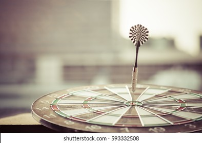 Dart arrow hitting in the target center of dartboard with modern city and sunset background. Target business, achieve and victory concept.