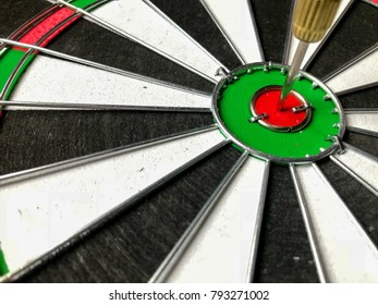 Dart arrow hitting in the target of dartboard on white background. Selective focus.