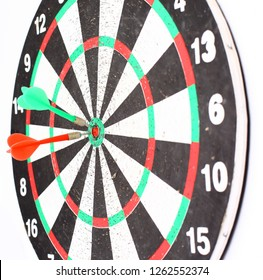 dart Board with a dart in the center of the target