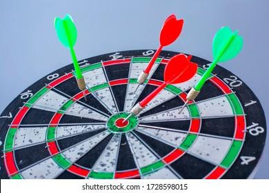 Dart board with color arrows hitting target, closeup