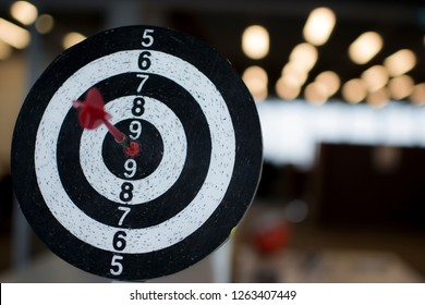 Dart board hanging with red dart hit at target on on bokeh light background, Business and technology goals
