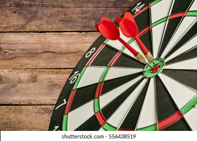 Dart board targeting the center on a wooden background