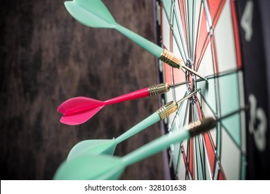 Dart in bulls eye of dartboard concept for hitting target dart success concept