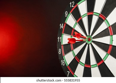 Dart in center of the target dartboard on a hot red background