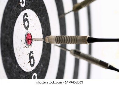 The dart game sticks out in the center of the red target an accurate hit to the target