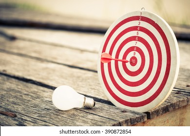 Dart hit the center of dartboard with light bulb