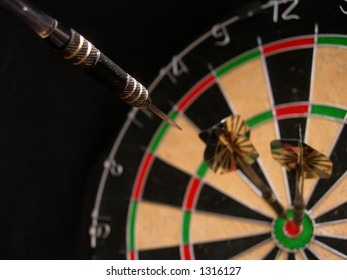 Dart hitting a dart board to make a hat-trick.
