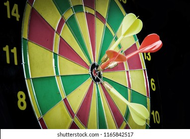 dart hitting a same target on red green and yellow colour dartboard to show concept same of target group