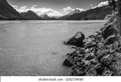 Dart River view in black and white with snow-capped mountains in the background at Isengard Lookout, a very remote location on Kinloch-Glenorchy Road in New Zealand, South Island.