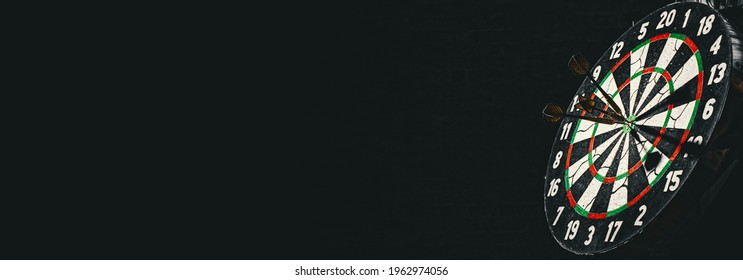 Dartboard with dart arrow hitting on a dark black background with copy space.