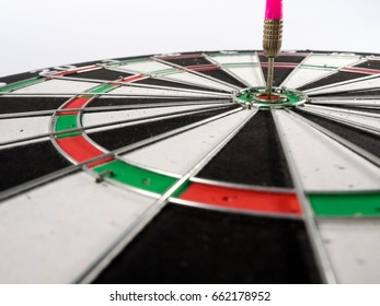 Dartboard with dart in the center target, success concept.