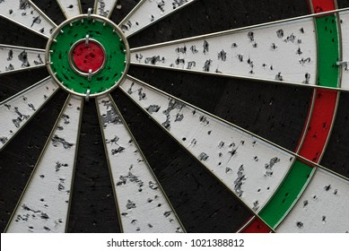 Dartboard with marks from dart throws. To succeed you must fail first. Succes comes after a lot of tries
