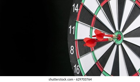 Dartboard on a black background with arrows hitting the center target