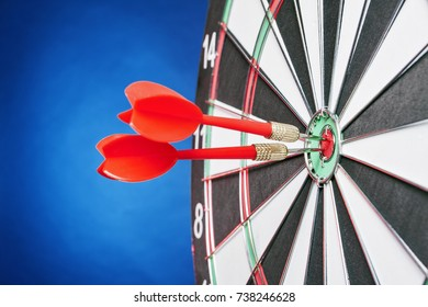 Dartboard on a blue background with arrows hitting the center target