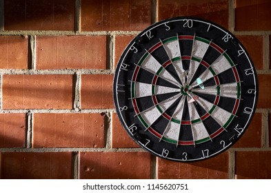 Dartboard on a brick wall. 3 darts in the bullseye. 150 bullseye