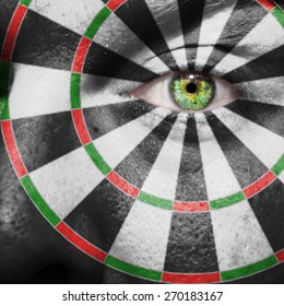 Dartboard painted on a man's face to support the game