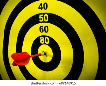Dartboard with a red dart hitting at the center