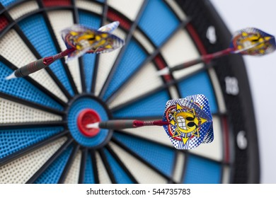 Dartboard with three darts, one hit bullseye with some selective focus