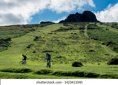 Dartmoor, Devon/ England - 8/19/2012: Cyclists prepare to ride up steep side of Hay Tor hill