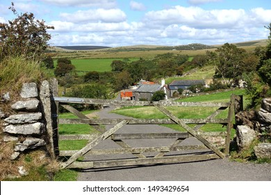 Dartmoor England. September 2019. Looking through a dilapidated five bar gate down a track to an old farm surrounded by trees. Moorland in distance. Blue sky light white clouds.
