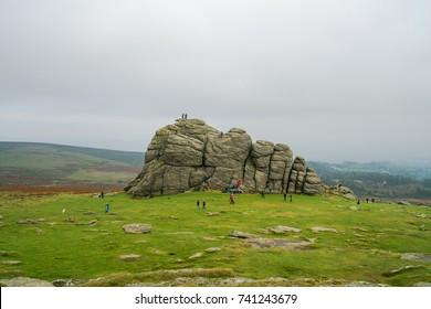 DARTMOOR, UK - OCTOBER 15, 201: Tourists visting Dartmoor National Park, climb Haytor Rocks. Haytor, Dartmoor's most famous landmark, is a granite tor on the eastern edge of Dartmoor in Devon, UK