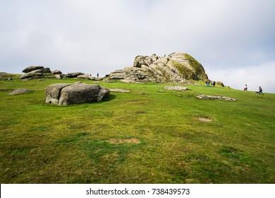 DARTMOOR, UK - OCTOBER 15, 2017: Tourists visting Dartmoor National Park, climb Haytor Rocks. Haytor, Dartmoor's most famous landmark, is a granite tor on the eastern edge of Dartmoor in Devon, UK