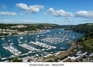 DARTMOUTH, DEVON, ENGLAND - AUGUST 30, 2017: View along River Dart Estuary and town of Dartmouth with Dartmouth Naval College in distance and yachts moored along blue river in morning sun