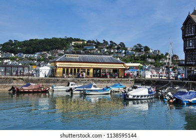 DARTMOUTH, DEVON/UK - June 23, 2018. Old station building restaurant and small boats, Dartmouth, South Devon, England