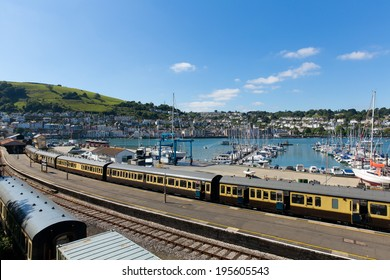 Dartmouth and Kingswear train station with colourful yellow carriages on railway track by marina with boats with blue sky and clouds in Devon England by the River Dart