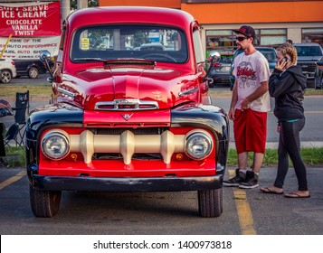 Dartmouth, Nova Scotia, Canada - August 16, 2018 : Young man looks at the interior of a 1951 Mercury pickup truck at  A&W weekly summer cruise-in, Woodside Ferry Terminal parking lot, Dartmouth.