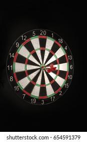 Darts hitting the center target on a dartboard