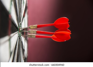 Darts hitting the center target on a dartboard