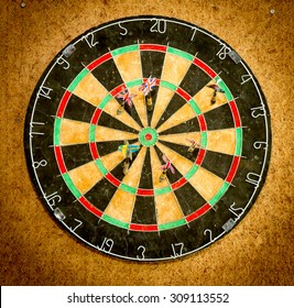 Darts on the dartboard hang on the wooden wall.