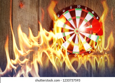 Darts on Dartboard at wall of wooden with flame, Business investment that rely on precision away be alert to success so game
