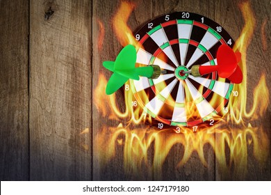 Darts on Dartboard at wall of wooden with flame, Business investment that rely on precision away be alert to success so game.