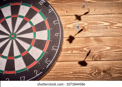 darts on a wooden background. three darts missed