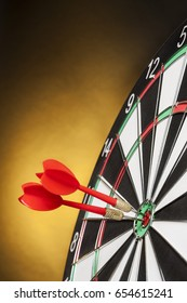 Darts targeting the center on a yellow background