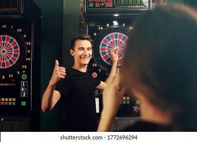 Darts. Young people throw darts at the target. Friendly game in a pub.
