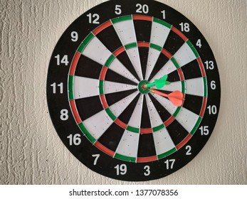 dartsboard with red and green darts on the wall