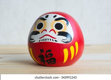Daruma doll japanese symbolise on wood table