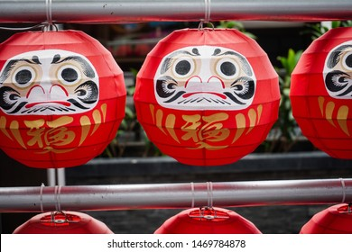 """Daruma dolls. The Japanese lucky symbolic dolls hanging in the row with text translation """"fortune""""."""