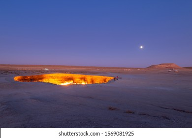 Darvaza Gas Crater in Turkmenistan, Central Asia after sunset. Also referred as the Door to Hell or Gates of Hell. Natural gas field set on fire. Moon, tourists and yurts visible in the desert.