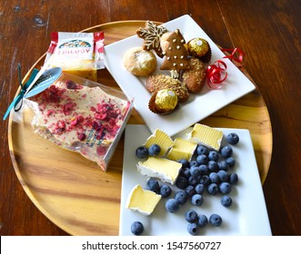 Darwin Australia December 2018: Chesses, blueberries and Christmas sweets on wooden dish close up shot.