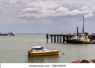 Darwin Australia - February 22, 2019: Closeup of anchored pilot boat with tugboats docked in back under blue sky with white cloudscape and gray seawater.