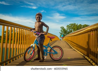 DARWIN, AUSTRALIA- MARCH 14, 2017: Australian Aboriginal boy enjoys the evening of summer hanging around on cycle in the bridge of Rapid Creek in Darwin, NT. He likes to ride a cycle in this outback.