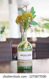 Darwin, Northern Territories/Australia - January 6 2019: an empty bottle of Archie Rose Signature Dry Gin is repurposed as a vase by a Darwin bar.