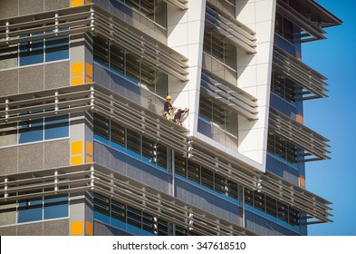 Darwin, Northern Territory-July 12, 2005.Two construction workers working on  a ledge on the outside of a new building,Darwin, Australia